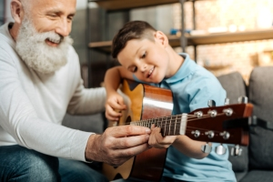 Smiling grandfather showing grandson how to play guitar
